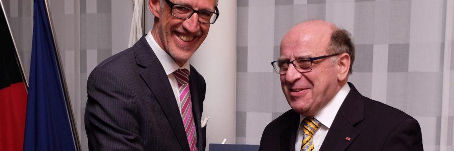 Der deutsche Botschafter und Jack Martin Händler mit dem Bundesverdienstkreuz